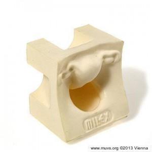 Parte de un kit de caja de anticonceptivos. Modelo de palpación blanco, formado en cubo, de la entrada vaginal y el cuello uterino.
